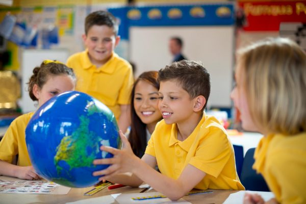 Four children in yellow T-Shirts look at a globe with their teacher